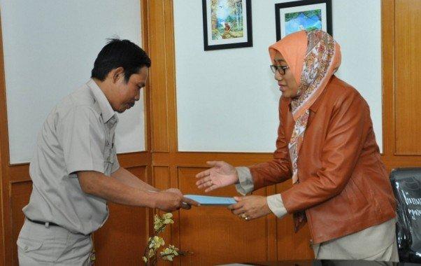Kepala Kantor Regional III BKN Bandung Istati Atidah (kanan) secara simbolis memberikan bantuan kepada pegawai BKN yang turut terkena banjir Bandung Selatan, Senin, (29/12/2014).